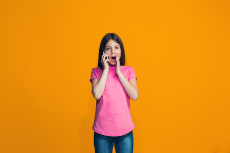 The happy teen girl standing and smiling against orange background. Standard-Bild