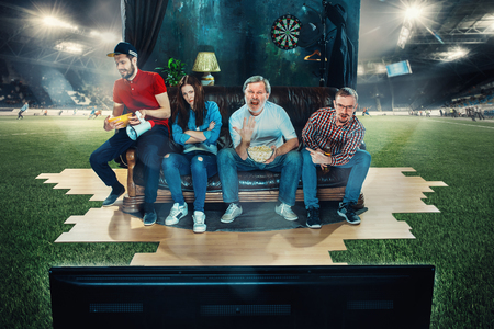 Soccer football fans sitting on the sofa and watching TV in the middle of a football field. Stock Photo