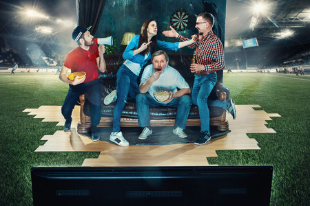 Soccer football fans sitting on the sofa and watching TV in the middle of a football field. Archivio Fotografico