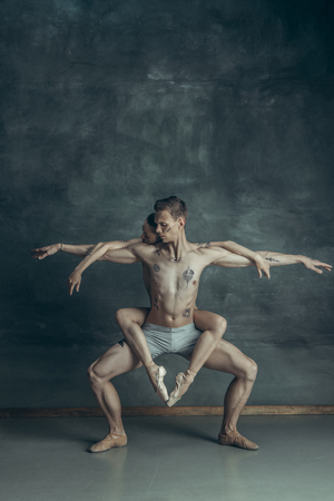 The young modern ballet dancers posing on gray studio background Stock Photo