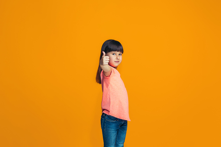 The happy teen girl standing and smiling against orange background. Stock Photo