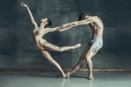The young modern ballet dancers posing on gray studio background Archivio Fotografico