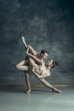 The young modern ballet dancers posing on gray studio background Banque d'images