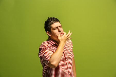 Isolated on green young casual man shouting at studio