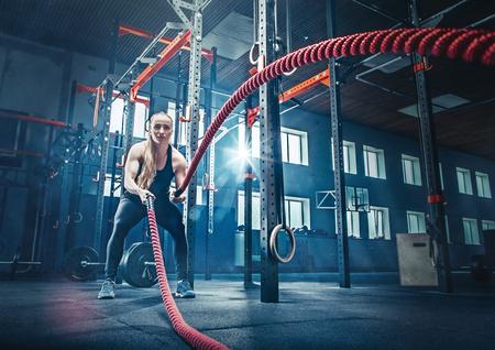 Vrouw met slag touw slag touwen oefenen in de fitnessruimte.