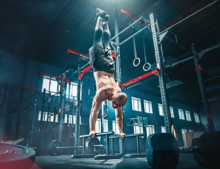 Concept: power, strength, healthy lifestyle, sport. Powerful attractive muscular man at CrossFit gym Stok Fotoğraf - 101832415
