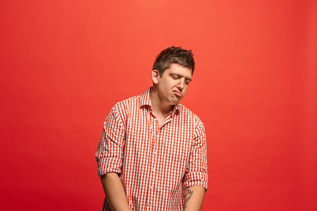 Beautiful bored man isolated on red background