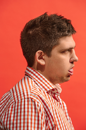 Doubtful pensive man with thoughtful expression making choice against red background