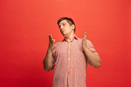 Beautiful male half-length portrait isolated on red studio backgroud. The young emotional surprised man
