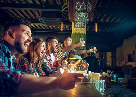 Concepto de deporte, gente, ocio, amistad y entretenimiento: aficionados al fútbol felices o amigos varones bebiendo cerveza y celebrando la victoria en un bar o pub