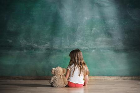 Meisje met teddybeer zittend op de vloer in lege ruimte. Autisme concept