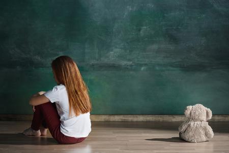 Kleines Mädchen mit Teddybär, der auf Boden in leerem Raum sitzt. Autismus-Konzept
