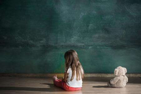 Kleines Mädchen mit Teddybär, der auf Boden in leerem Raum sitzt. Autismus-Konzept Standard-Bild