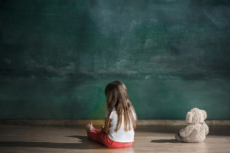 Little girl with teddy bear sitting on floor in empty room. Autism concept