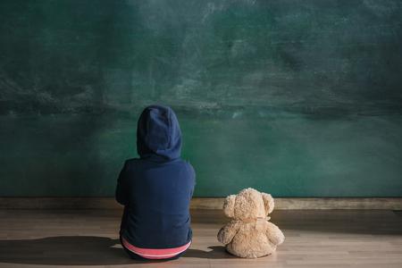 Dziewczynka z misiem siedzi na podłodze w pustym pokoju. Koncepcja autyzmu