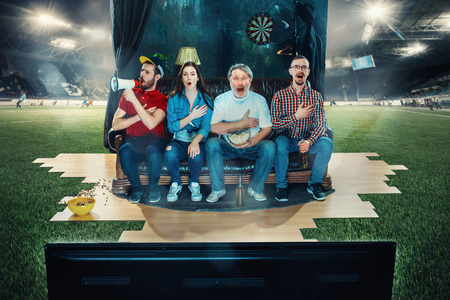 Soccer football fans sitting on the sofa and watching TV in the middle of a football field. Stok Fotoğraf
