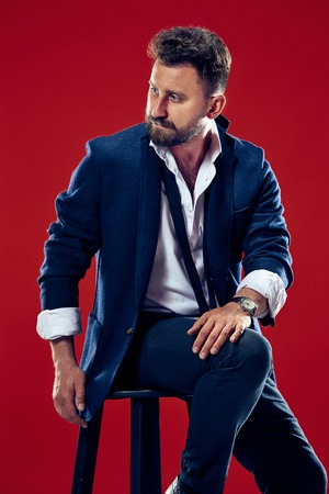 Male beauty concept. Portrait of a fashionable young man with stylish haircut wearing trendy suit posing over red background. Archivio Fotografico - 102157468