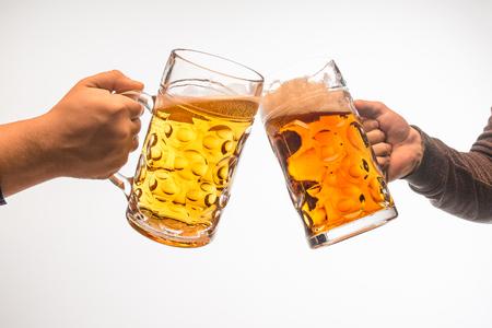 Manos con tazas de cerveza vertiendo salpicaduras de salpicaduras aisladas sobre fondo blanco Foto de archivo - 102157655