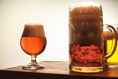The two mugs of beer on table background