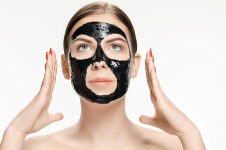 Young beautiful woman applying a mask for the face of the therapeutic black mud. Spa treatment Banque d'images - 102186761