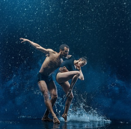 Young couple of ballet dancers dancing unde rwater drops Фото со стока