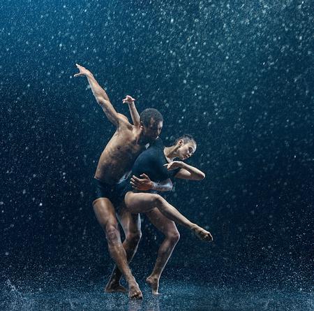 Junges Paar Balletttänzer, die unter Wassertropfen tanzen