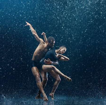 Young couple of ballet dancers dancing unde rwater drops 스톡 콘텐츠