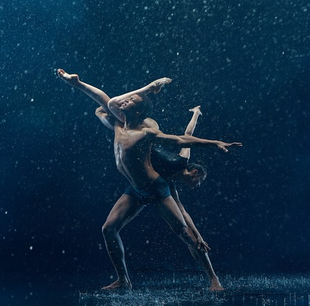 Young couple of ballet dancers dancing unde rwater drops Imagens