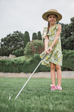 Little girl just swing golf ball on golf course fairway Archivio Fotografico - 102613342