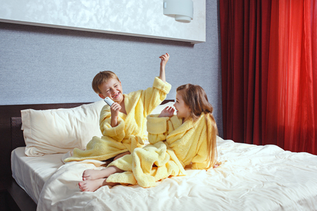 Happy laughing kids, boy and girl in soft bathrobe after bath play on white bed Stockfoto