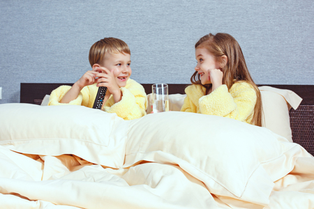 Happy laughing kids, boy and girl in soft bathrobe after bath play on white bed Stock Photo