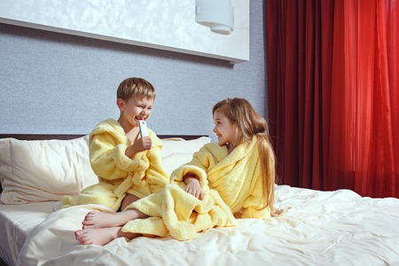 Happy laughing kids, boy and girl in soft bathrobe after bath play on white bed Stock Photo - 102679469