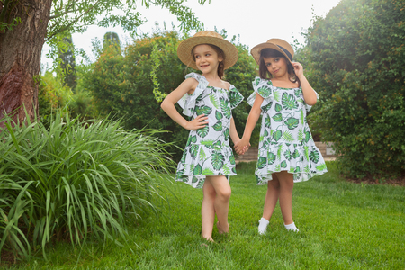 Portrait of smiling beautiful girls with hats against green grass at summer park.