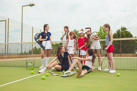 Portrait of group of girls as tennis players holding tennis racket against green grass of outdoor court Zdjęcie Seryjne