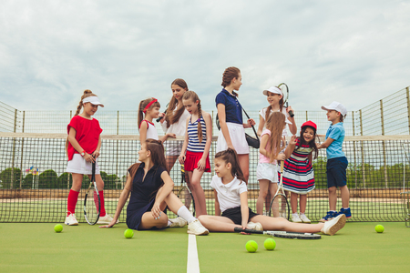Portrait of group of girls as tennis players holding tennis racket against green grass of outdoor court Banque d'images