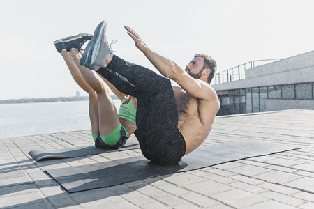 Fit fitness woman and man doing stretching exercises outdoors at city Stock Photo