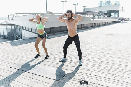 Fit fitness woman and man doing fitness exercises outdoors at city Stok Fotoğraf - 102924774