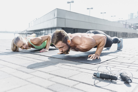 Fit fitness woman and man doing fitness exercises outdoors at city Stok Fotoğraf - 102925282