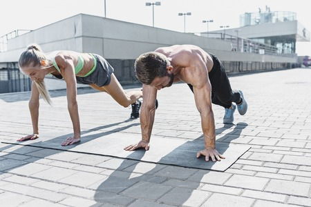 Fit fitness woman and man doing fitness exercises outdoors at city Stok Fotoğraf - 102925294