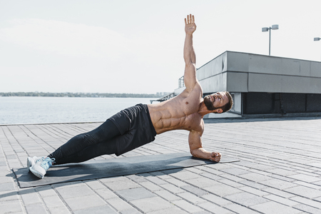 Fit fitness man doing fitness exercises outdoors at city Stok Fotoğraf - 102925295