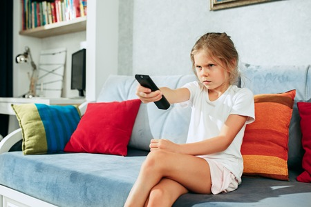 Little casual girl watching tv at home. Female kid sitting on sofa with TV remote and switching channels