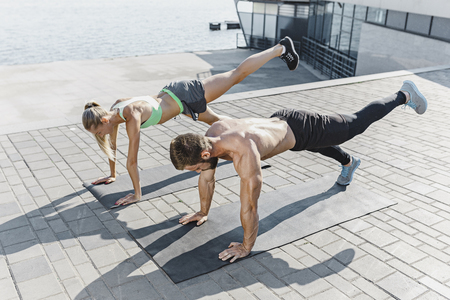 Fit fitness woman and man doing fitness exercises outdoors at city Stok Fotoğraf - 103107087