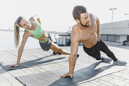 Fit fitness woman and man doing fitness exercises outdoors at city Stok Fotoğraf