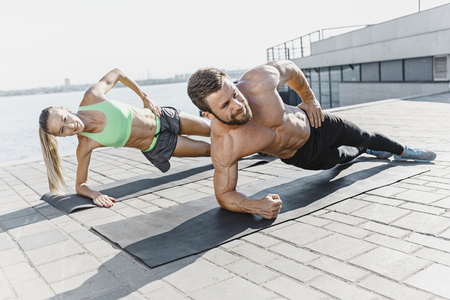 Fit fitness woman and man doing fitness exercises outdoors at city Stok Fotoğraf - 103107188