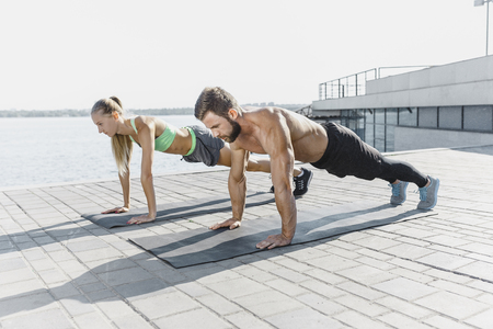 Fit fitness woman and man doing fitness exercises outdoors at city Stok Fotoğraf - 103107189