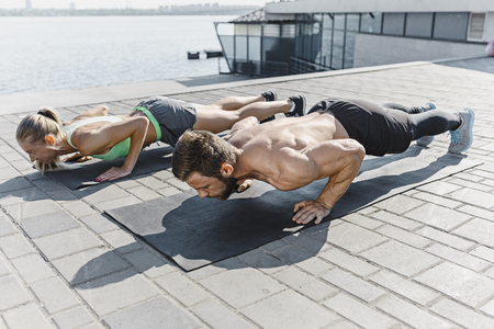 Fit fitness woman and man doing fitness exercises outdoors at city Stok Fotoğraf - 103107190