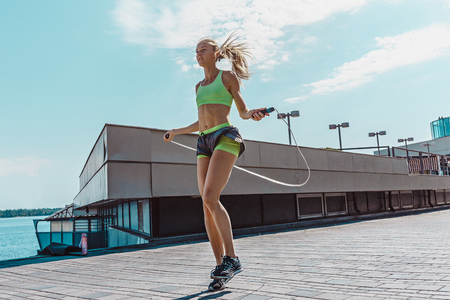 Fit fitness woman doing fitness exercises outdoors