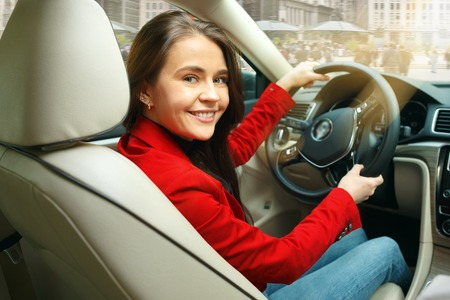 Driving around city. Young attractive woman driving a car