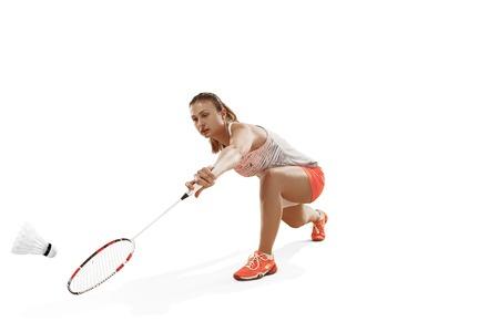 Mujer joven jugando al bádminton sobre fondo blanco.