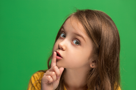 The young teen girl whispering a secret behind her hand over green background
